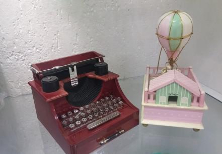 6- Fofíssimas, as caixinhas de música custam R$ 40 (máquina de escrever) e R$ 47 (casinha com balão), respectivamente.