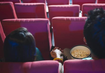 mv-a-movie-hall-theater-popcorn-couple-holding-hands