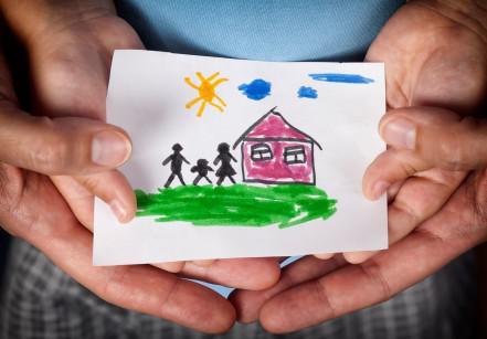 #ParaCegoVer: as mãos de uma criança e de um adulto, juntas, seguram o desenho de uma família em frente à uma casa rosa em um dia de sol.