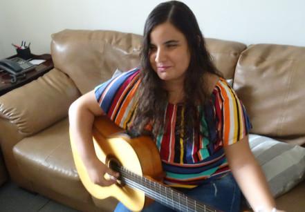 #PraCegoVer: Ao fundo uma parece branca. Mari está sentada em um sofá tocando violão