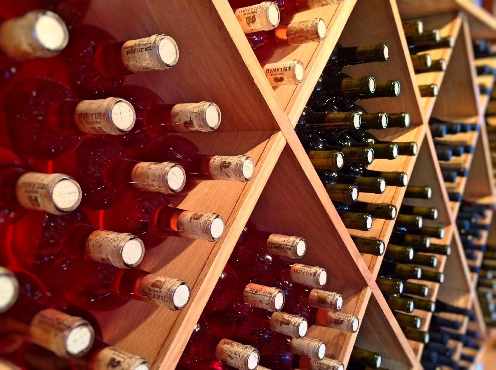 #PraCegoVer: Garrafas de vinho estão dispostas em uma adega.