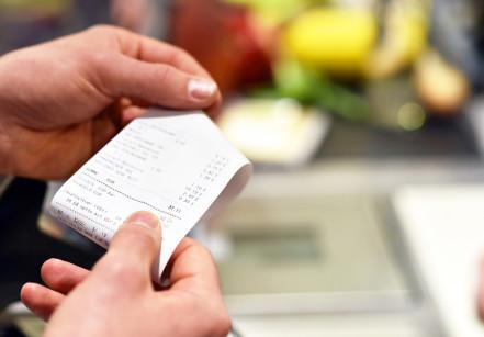 Hnde mit Kassenzettel an der Kasse im Supermarkt // hands with receipt at the checkout in the supermarket
