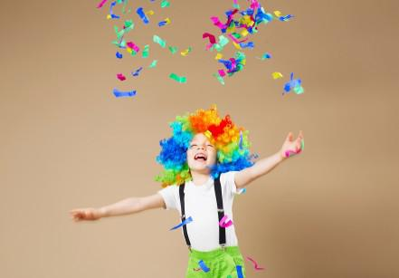Happy clown boy in large colorful wig. Let's party! Funny kid clown. 1 April Fool's day concept.