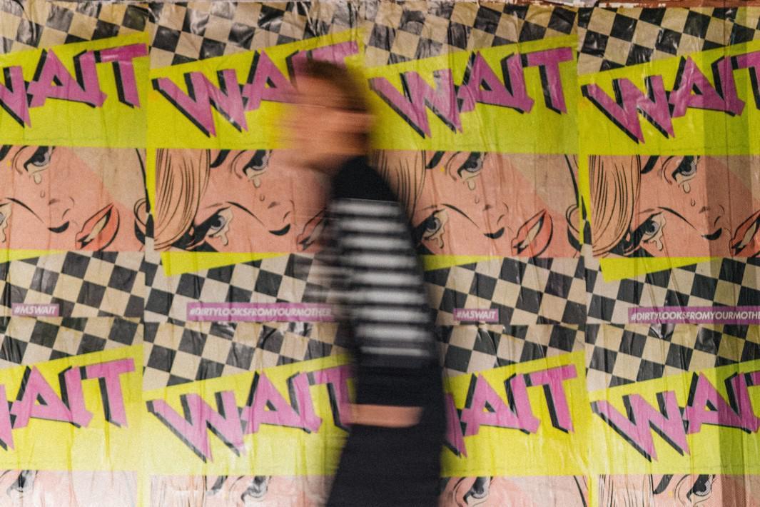 www.juicysantos.com.br - homem andando rapidamente em muro grafitado