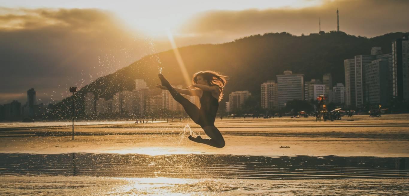 Na imagem uma bailarina dança ao por do sol na praia de Santos, SP. Em um salto, ela expressa um movimento belo com prédios e montanhas ao fundo. Esta foto foi publicada originalmente no Instagram do Juicy Santos.