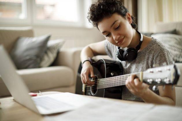 www.juicysantos.com.br - garota tocando violão vendo aula online no computador para ilustrar aulas de música ao vivo da spotlight escola de músicos online