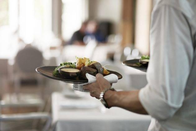 www.juicysantos.com.br - como será o turismo em santos depois da pandemia - curso ensina - garçom levando prato para a mesa no restaurante