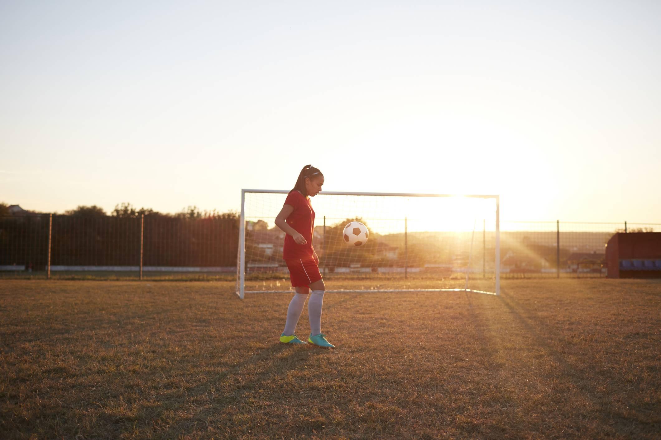 www.juicysantos.com.br - futebol feminino - menina jogando futebol em gramado ao por do sol